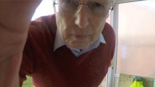 Alan olha para uma câmera