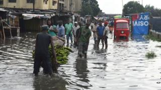 People walk on a flooded road at Okokomaiko in Ojo district of Lagos, on May 31, 2017.
