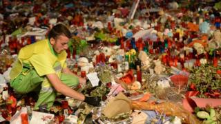 A municipal worker removes flowers from a tribute in memory of the victims of the Las Ramblas attack, Barcelona, 28 August 2017