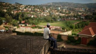 A man sits as the evening sun falls over the Kicukiro District of the capital April 5, 2014 in Kigali, Rwanda.