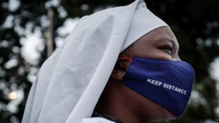 A worshipper of Legio Maria wears a protective face mask with the lettering 'Keep distance' as she arrives to attend a prayer at their church in the Kibera slum of Nairobi, on July 26, 2020, after Kenya's President allowed places of worship to reopen under strict guidelines to curb the spread of the novel coronavirus (COVID-19).