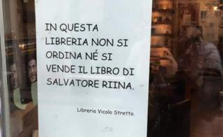 The sign in Italian reading: In this bookshop Salvatore Riina's book will not be ordered nor sold