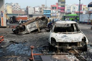 "Local residents look at burnt-out vehicles following clashes between people supporting and opposing a contentious amendment to India""s citizenship law, in New Delhi on February 26, 2020"