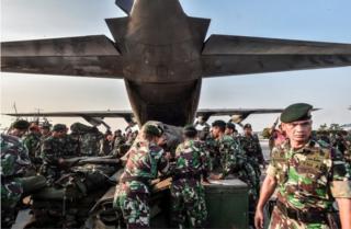 Индонезийские солдаты загружают гуманитарную помощь в самолет