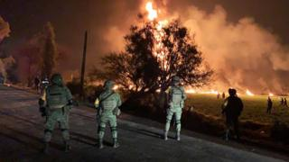 Army personnel look over site of large fire