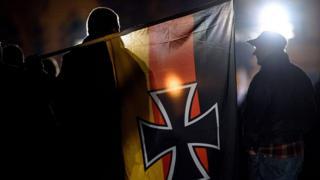"""Alman aşırı sağcılar gösterilerinde üzerinde siyah """"demir haç"""" sembolü olan bayraklar taşıyor."""