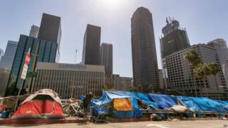 Tents used by the homeless line a downtown Los Angeles street with the skyline behind Tuesday, on 22 September 2015