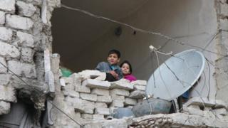 In this Thursday, Feb. 11, 2016 photo, children peer from a partially destroyed home in Aleppo, Syria.