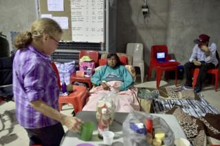A family relaxes in a temporary cyclone shelter in the town of Ayr in far north Queensland as Cyclone Debbie approaches on 28 March 2017.