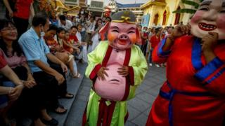 Performers in costumes of a pig (C) and other traditional Chinese characters entertain tourists at a temple during a performance to celebrate the Lunar New Year, or Spring Festival, in Chinatown in Bangkok