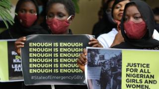 """Protesters wearing face masks hold banners saying """"enough is enough"""" and """"justice in Nigeria for women and girls""""."""