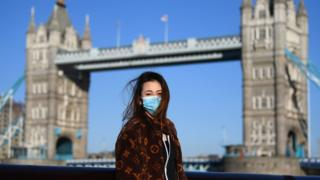 A member of the public poses for a photo in front of Tower Bridge whilst wearing a protective mask on March 22, 2020 in London.