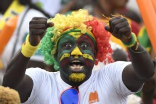 A Senegal supporter whose face is painted in the colours of the country's flag cheers ahead of the match.