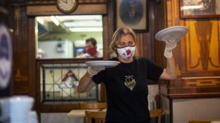 A woman in a cafe carrying plates