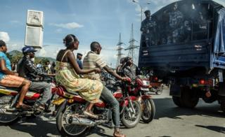 People ride motorbikes behind a truck transporting security forces in Bujumbura on 15 May 2015