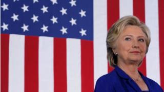 Hillary Clinton o flaen baner yr UDA