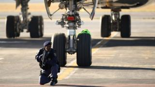 Armed Police officers guard the plane before the players disembark as the England team arrive at Johannesburg's OR Tambo International Airport for the 2010 FIFA World Cup on June 3, 2010 in Johannesburg, South Africa.