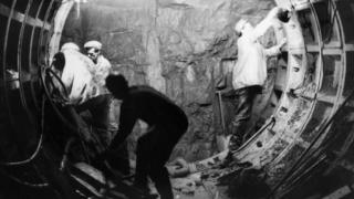 Men fit metalwork in tunnel