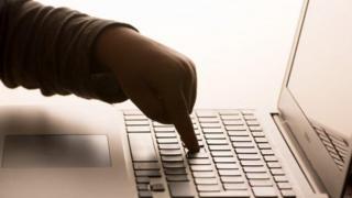 Child's hand on computer