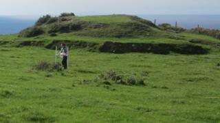 A scientist surveying a Round Mound on the Isle of Man