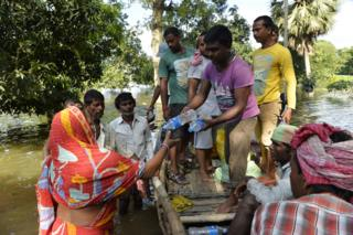 Indian flood effected villagers collect drinking water and relief food at Alal village in Malda district in the Indian state of West Bengal on August 23, 2017. More than 750 people have died in floods across South Asia, officials said August 21.