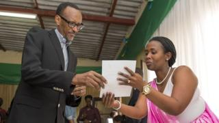 Rwanda President Paul Kagame is guided by polling assistants as he votes in Rwanda's capital, Kigali, on 18 December 2015