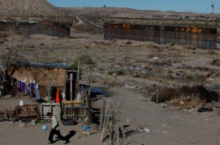 A child plays with a ball at his house as a newly built section of the US-Mexico border fence is seen in the background at Anapra neighbourhood in Ciudad Juarez, Mexico
