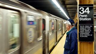 A commuter waits at New York City's Penn Station as a subway train approaches.