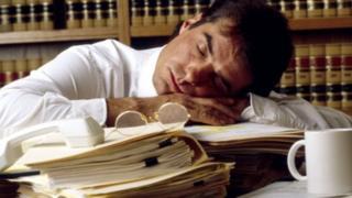 موظف نائم على مكتبه أثناء العمل