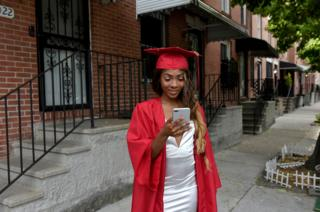 Francina Townes, 18, dressed for her high school graduation from Woodlawn High School, looks at her mobile phone while standing in front of her house