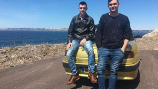 Pierre Fouchard (L) and Alex Bry (R) sitting atop Pierre's Peugeot overlooking Étang de Savoyard on Saint-Pierre island.