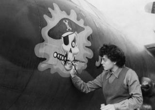 Private First Class Barbara O'Brien applies the finishing touches to a skull on the nose of a B-26 Marauder