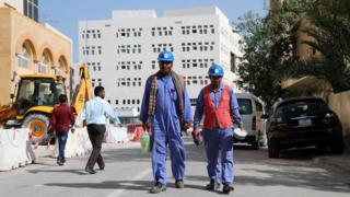 Migrant workers walk next to a construction site in Doha, Qatar (6 December 2016)