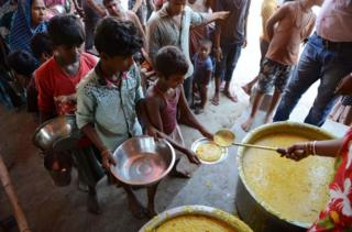 Indian villagers queue for food
