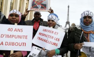 "Djiboutian holding placards reading (L-R): ""40 years of impunity in Djibouti"" and ""Free and respect workers"" in Paris, France - Saturday 25 February 2017"