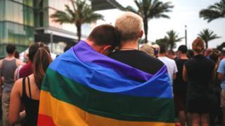 Dos hombres envueltos en una bandera del movimiento gay en Orlando, Florida
