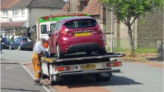 A burgundy Ford Fiesta on the back of a lorry