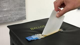 Someone places their vote in a ballot box during Guernsey's 2018 referendum