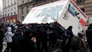 Demonstrators overturn a container during a demonstration against the pension overhauls, in Paris, on 5 December, 2019.