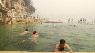 Swimmers at a Sydney beachside pool amid the smoke on Tuesday morning