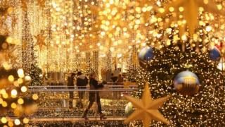 Shoppers walk among Christmas lights in Berlin