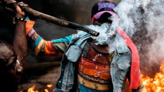 One man hold stick wey dey burn as I-no-gree-people dey riot for Kibera, Nairobi on 25/10/2017