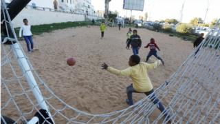 Libyan youths play a game of football on a sand pitch in the capital Tripoli, on 3 February 2020