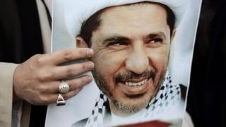 محتج يحمل صورة الشيخ على سلمان