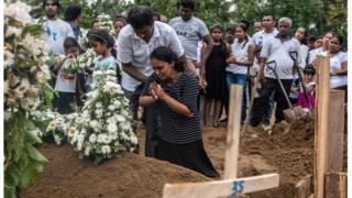 Una mujer llora en una de las tumbas donde fueron sepultadas algunas de las víctimas fatales de los atentados del pasado domingo.