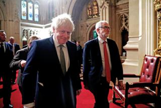 Prime Minister Boris Johnson (left) and Labour Party leader Jeremy Corbyn walk through the Peers Lobby