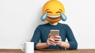 Persona con cabeza de emoji sonriente.