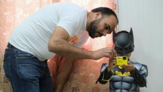 Charity worker with child refugee dressed as Batman