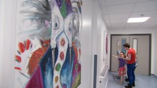 Sadie and her mum Pauline look at a painting of a snail at the Royal Hospital for Sick Children