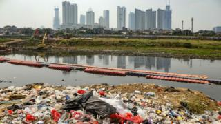 Plastic waste on the banks of a river with a view of the Jakarta skyline (file photo - August 2019)